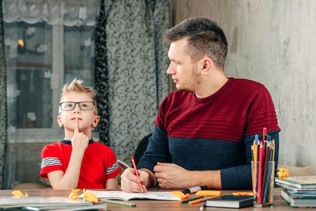 De vader helpt zijn zoon huiswerk te maken voor de school.