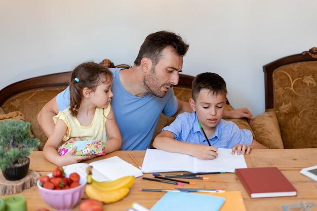 De vader helpt zijn zoon met huiswerk, zorgt ervoor dat de jongen correct schrijft, terwijl de jongste dochter in zijn armen zit.