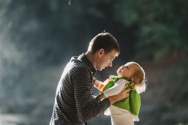 De vader houdt van handen zijn dochter in het park