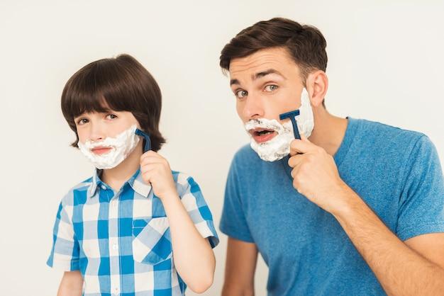 De vader laat zijn zoon zien hoe hij zich in de badkamer moet scheren.