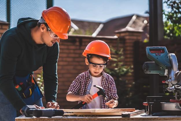 De vader laat zijn zoontje zien hoe hij een hamer moet gebruiken
