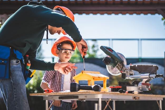 De vader leert zijn zoon een schroevendraaier te gebruiken