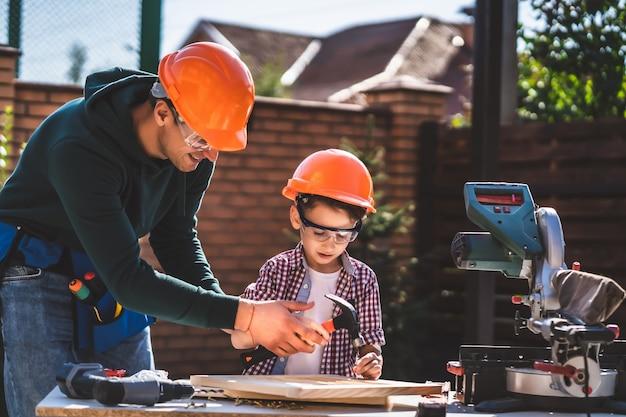 De vader leert zijn zoon hamer en spijkers te gebruiken