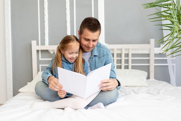 De vader leest een boek of studeert met het kind van de dochter voordat hij naar bed gaat of heeft plezier