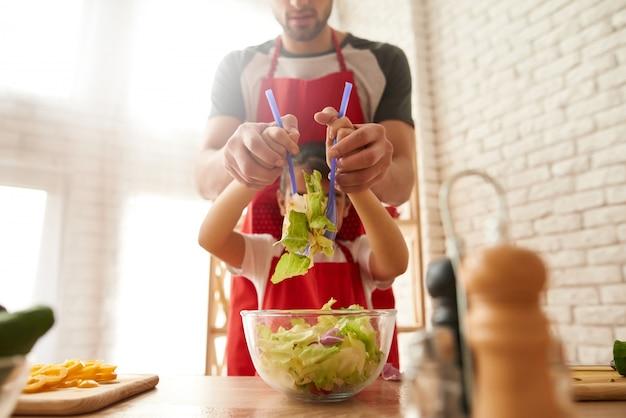 De vader met dochter kookt salade op keuken.