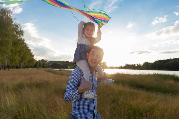 De vader met dochter met vlieger bij zonsondergang