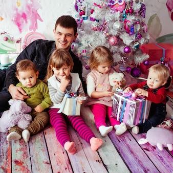 De vader met kinderen zit in de buurt van de kerstboom