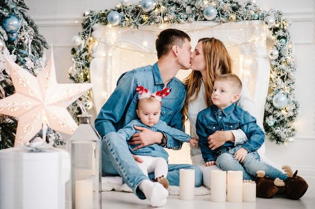 De vader, moeder knuffelen zoontje en dochter in de buurt van de kerstboom. vrolijk kerstfeest. kerst versierd interieur. het concept van gezinsvakantie. detailopname.
