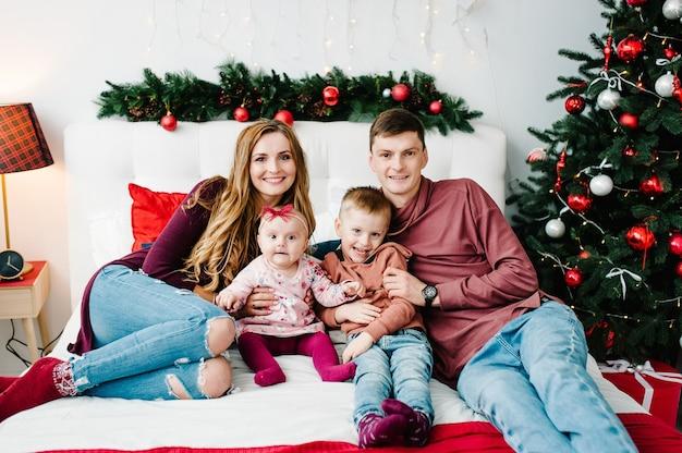 De vader, moeder knuffelen zoontje en dochter op bed in de slaapkamer in de buurt van de kerstboom. vrolijk kerstfeest. kerst versierd interieur. het concept van gezinsvakantie. detailopname.
