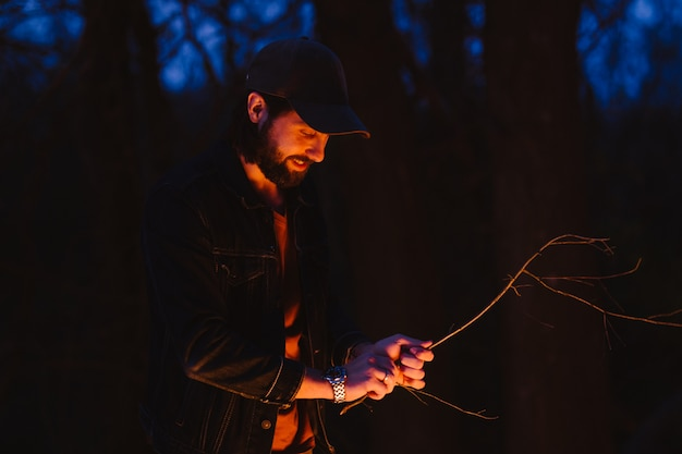 De vader staat 's nachts voor een vuur in het bos met takjes in zijn hand. .