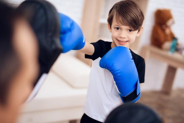 De vader traint zijn zoon boksen.