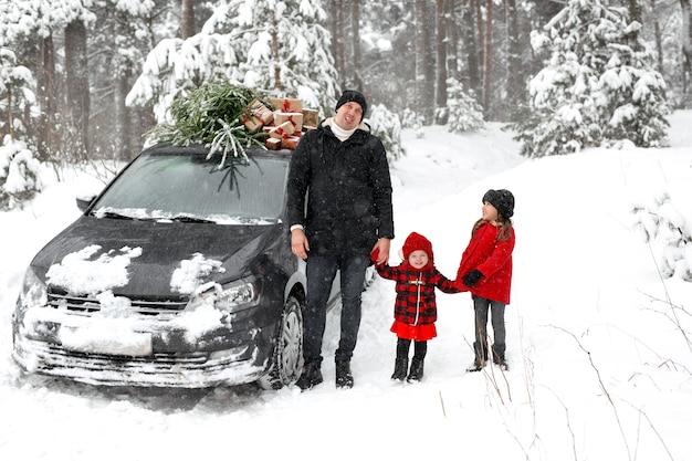 De vader trekt een grimas en toont zijn tong aan de kinderen naast de kerstboom