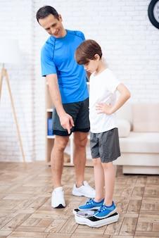 De vader weegt zijn zoon op de weegschaal.