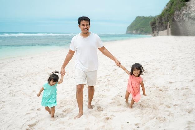 De vadergreep overhandigt dochter twee op het strand