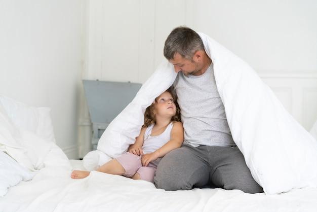 De vaderzitting van het vooraanzicht met dochter onder deken