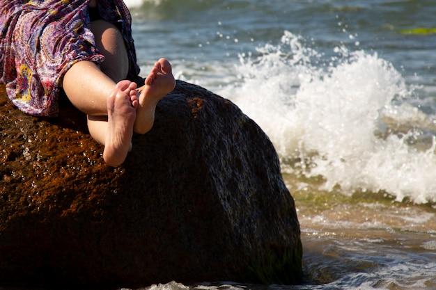 De vakantie vakantie. vrouw benen close-up van een meisje zittend op een grote rots aan de kust, golven en spatten van water aan haar voeten op zonnige zomerdag.
