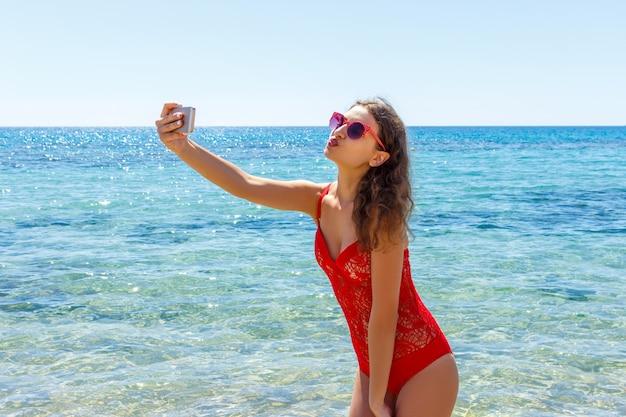 De vakantiemeisje die van het de zomerstrand pret mobiele selfiefoto met smartphone nemen.