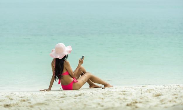 De vakantiemeisje die van het strand aan muziek in hoofdtelefoons op een mobiele telefoon tijdens de zomer luisteren