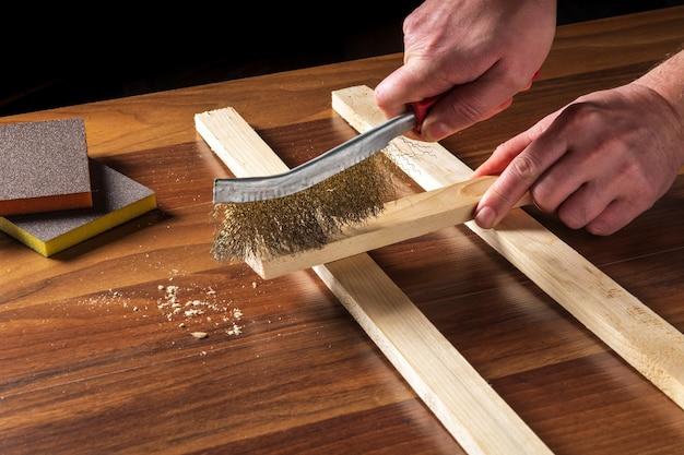 De vakman maakt de houten plank schoon met een schuurmiddel.