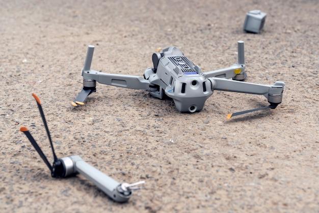 De val van de drone. een kapotte vliegende quadcopter ligt op het asfalt, de propeller is eraf gevlogen en de camera is beschadigd.