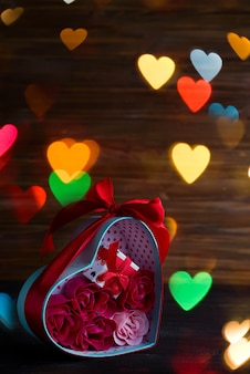 De valentijnskaartenachtergrond met rode harten en nam in giftdoos toe op donkere houten achtergrond