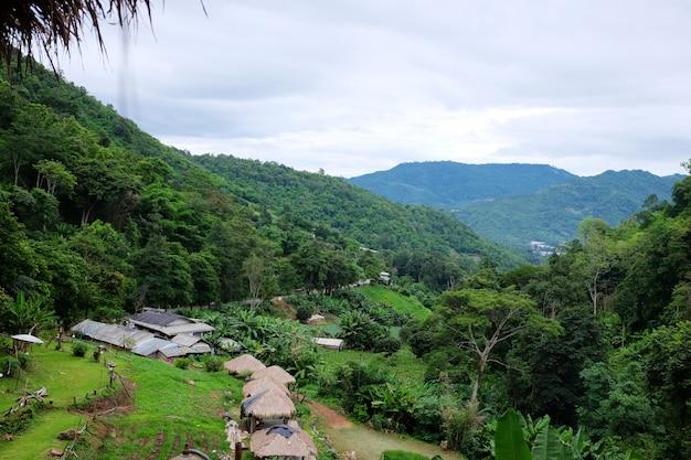 De valleiberg van het landschap met het dorp van de heuvelstam op groene heuvel en bos in regenachtig seizoen