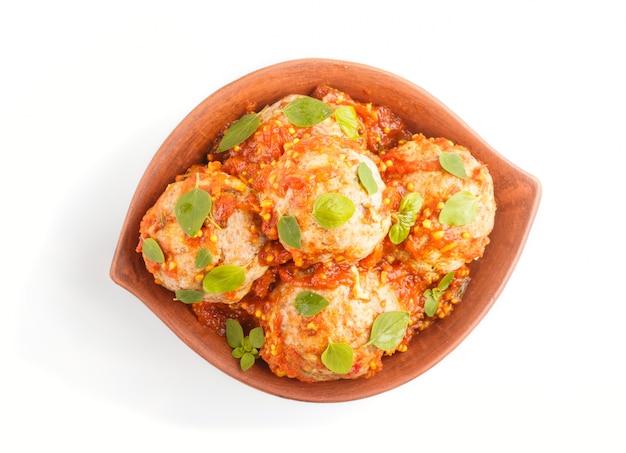 De varkensvleesvleesballetjes met tomatensausorego verlaat kruiden en kruiden in kleikom op witte achtergrond wordt geïsoleerd die