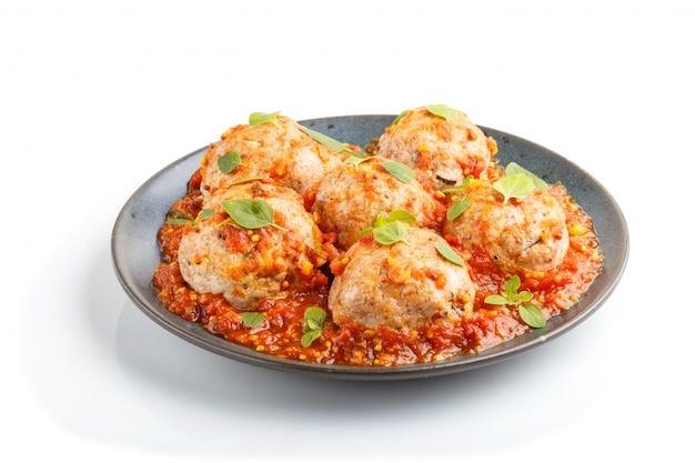De varkensvleesvleesballetjes met tomatensausorego verlaat kruiden en kruiden op blauwe ceramische plaat die op witte achtergrond wordt geïsoleerd