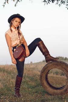 De veedrijfster van het meisje in het overhemd van jeanslaarzen en met een zak in een doos met een wiel bij een boom