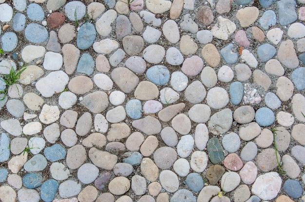 De veelkleurige kiezelstenen in het tuinpad als achtergrond