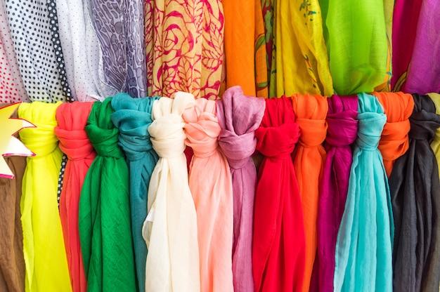 De veelkleurige sjaals hangen aan een houten hanger.