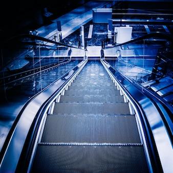 De veelvoudige stappen en de richtingen van een roltrap in het moderne winkelcomplex, zwart-witte achtergrond