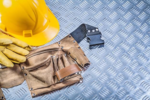 De veiligheid van de hulpmiddelriem gloves bouwvakker op golfmetaal achtergrondbouwconcept