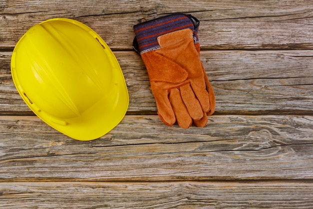 De veiligheidshandschoenen van de bouwwerfveiligheid beschermende bouwvakker op houten achtergrond
