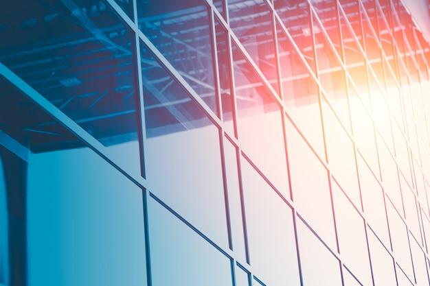 De vensters die van het bedrijfsbureauglas met zon bouwen voor moderne bouwachtergrond nadenken
