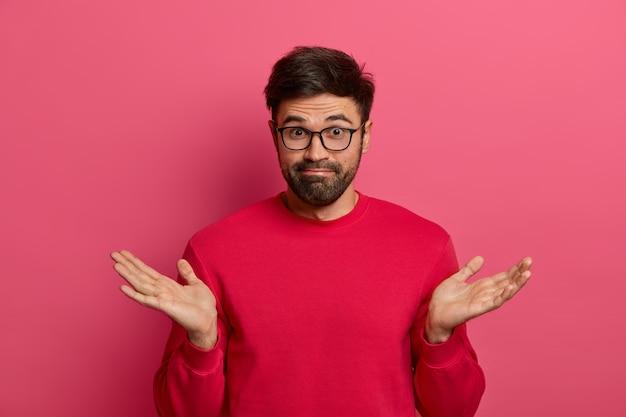 De verbaasde aarzelende man met baard haalt aarzelend zijn handen op