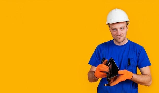De verbaasde arbeider in overall houdt zijn lege portemonnee zonder geld. het concept van economische crisis, werkloosheid en productie, coronavirus, pandemie, gezondheid