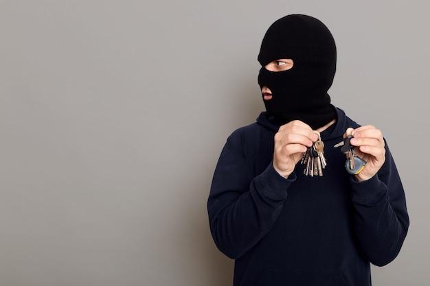 De verbaasde criminele dief kijkt zijdelings en met een tevreden uitdrukking op zijn gezicht