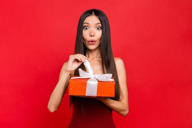 De verbaasde dame bekijkt camera ontvangt giftbox die op rode muur wordt geïsoleerd