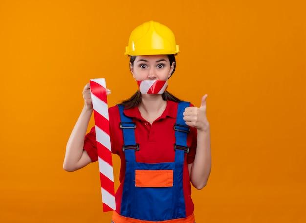 De verbaasde jonge mond van het bouwersmeisje verzegeld met waarschuwingsband houdt plakband en duimen omhoog op geïsoleerde oranje achtergrond met exemplaarruimte