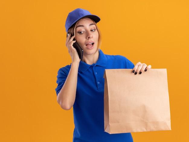 De verbaasde jonge mooie leveringsvrouw in uniform houdt document pakket en spreekt over telefoon die op oranje muur wordt geïsoleerd
