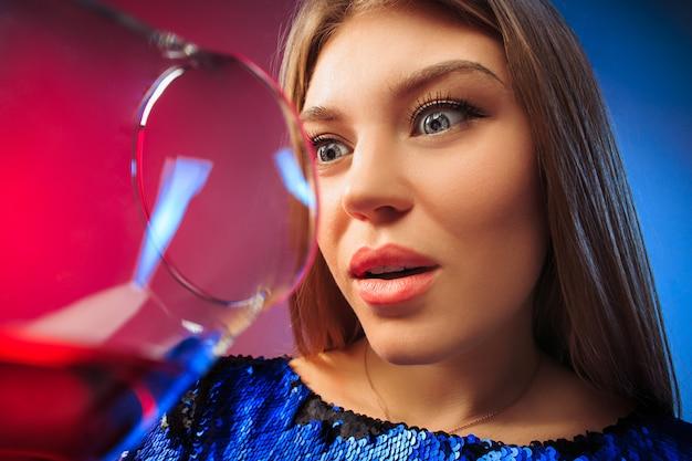 De verbaasde jonge vrouw in feestkleding poseren met glas wijn