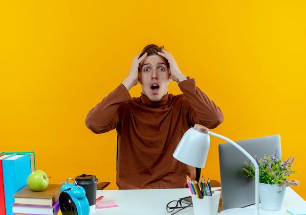 De verbaasde jonge zitting van de studentenjongen aan bureau met schoolhulpmiddelen greep hoofd op geel
