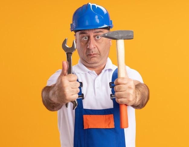 De verbaasde kaukasische volwassen bouwersmens in uniform houdt moersleutel en hamer op sinaasappel