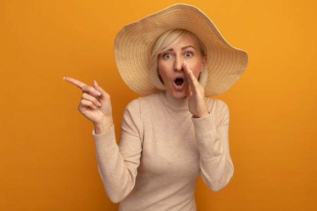 De verbaasde mooie blonde slavische vrouw met strandhoed houdt de hand dicht bij de mond en wijst naar de zijkant op oranje