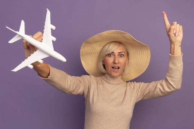 De verbaasde mooie blonde slavische vrouw met strandhoed houdt modelvliegtuig vast en wijst op paars