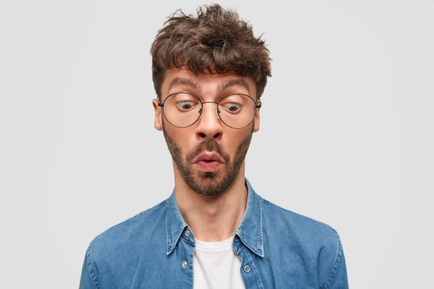 De verbaasde ongeschoren man vraagt zich af terwijl hij iets merkt, een ontevreden uitdrukking heeft, een bril en een shirt draagt