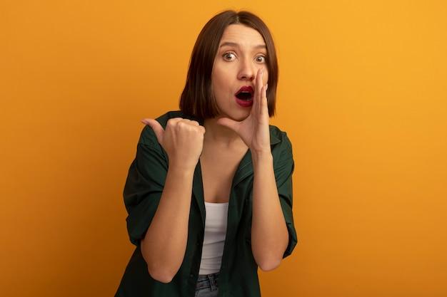 De verbaasde vrij blanke vrouw houdt de hand dicht bij de mond en wijst naar de zijkant op oranje