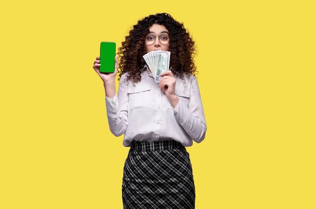 De verbaasde vrouw in glazen houdt stapel dollars en smartphone met leeg groen scherm over gele geïsoleerde achtergrond. concept van online casino, weddenschappen, games
