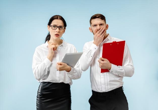 De verbaasde zaken man en vrouw lachend op een blauwe muur